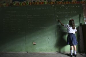 A girl writes on a chalk board during the opening of the elementary school year in the old center of Managua February 4, 2008. REUTERS/Oswaldo Rivas (NICARAGUA) - RTR1WP1F